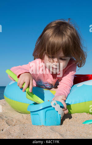 little cute girl sits in a children's pool on the beach - Stock Photo