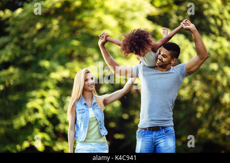 Picture of happy young couple spending time with their daughter - Stock Photo