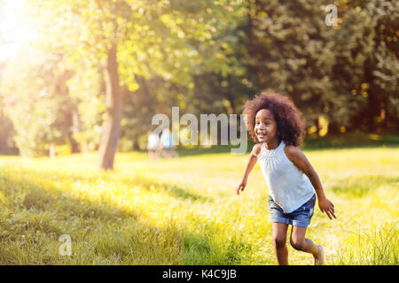 Portrait of happy little girl running on grass land - Stock Photo
