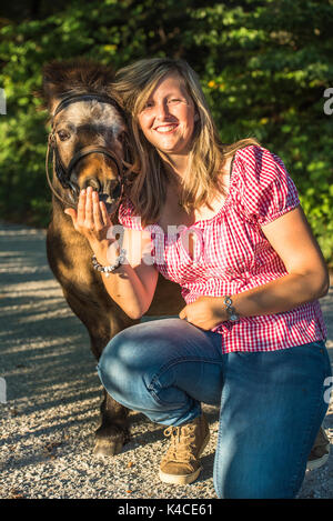 Laughing Young Blond Woman Head To Head With Brown Shetland Pony - Stock Photo