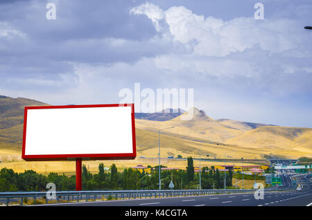Blank white billboard on the background of the highway - Stock Photo