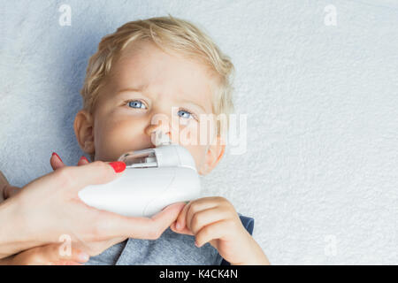 Mother using baby electric nasal aspirator. She is doing a mucus suction to twenty months baby boy. - Stock Photo