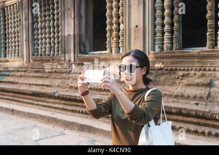 Female traveler taking photo with her smartphone in angkor wat siem reap cambodia - Stock Photo