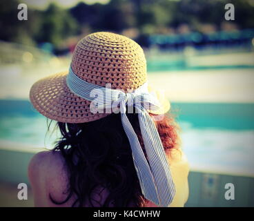 Pretty woman wearing a straw hat and she relaxes in the exclusive luxurious tourist resort on the edge of the pool - Stock Photo