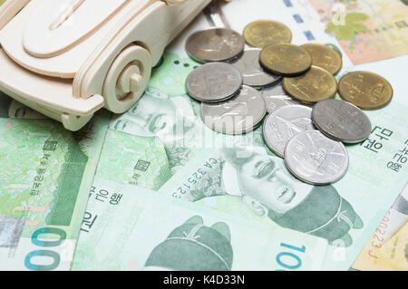 Wooden car and Korean money. Concept for buying, renting, insurance, fuel, service and repair costs. - Stock Photo