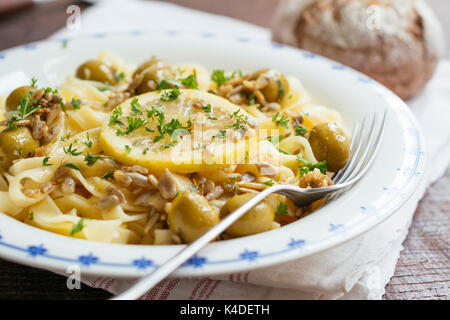 Sicilian tagliatelle pasta with lemon, garlic and olives, garnished with sunflower seeds. - Stock Photo