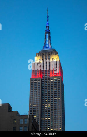 Empire State Building at night, showing the colors of the American flag: red, white and blue - Stock Photo