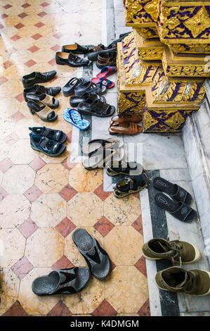Shoes left outside the entrance to the Marble Temple / Wat Benchamabophit Dusitvanaram  in Bangkok, Thaiand. - Stock Photo