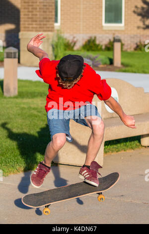 Young man doing skateboard tricks on a sidewalk in summer - Stock Photo