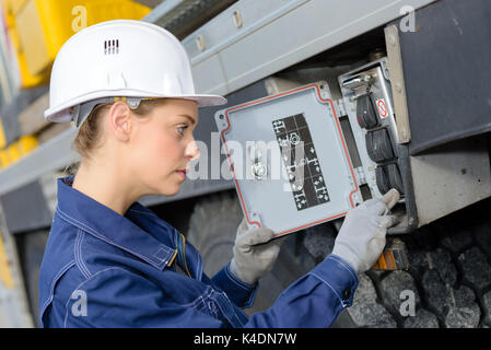 woman electrician engineer inspecting electric counter utdoors - Stock Photo