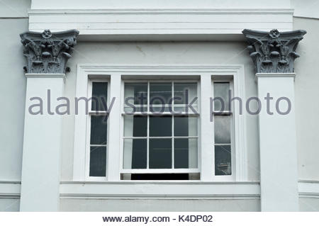Ornate pillars either side of a sash window , Poole, Dorset, England - Stock Photo