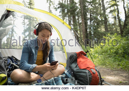 Teenage girl relaxing, camping and listening to music with headphones and mp3 player in tent - Stock Photo