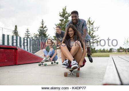 Playful teenage friends playing, pushing skateboards at skate park - Stock Photo