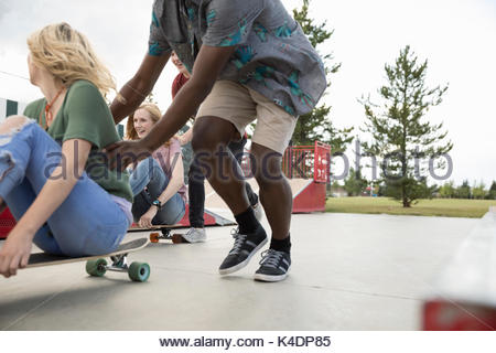 Teenage friends playing, pushing skateboards in skate park - Stock Photo