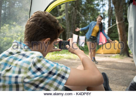 Teenage boy with camera phone photographing girl outside tent at outdoor school campsite - Stock Photo