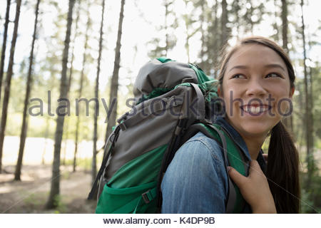 Portrait smiling teenage girl with backpack hiking in woods - Stock Photo