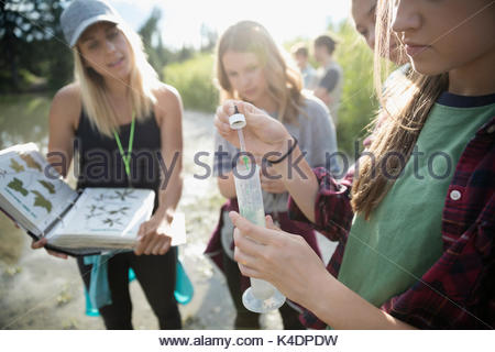 Female teacher and teenage girl outdoor school students conducting scientific experiment in nature - Stock Photo