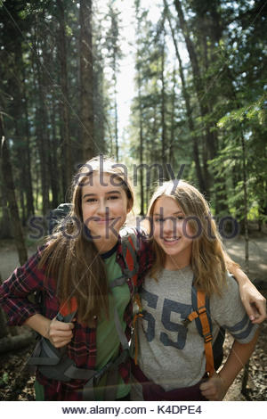 Portrait confident, smiling teenage girl friends hiking in woods - Stock Photo
