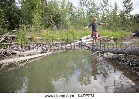 Teenage boy walking, balancing on fallen log over river in woods - Stock Photo