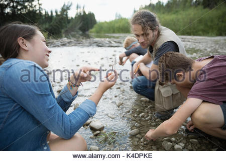 Male teacher and teenage outdoor school students collecting water samples at stream - Stock Photo