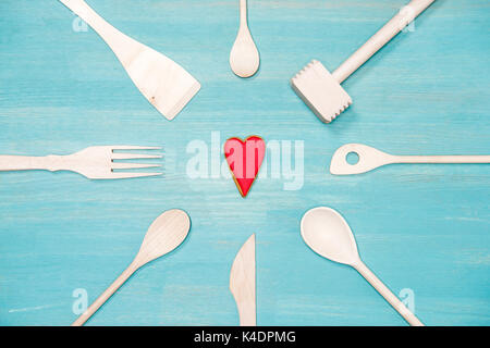 top view of various wooden cooking utensils with heart symbol on blue tabletop - Stock Photo