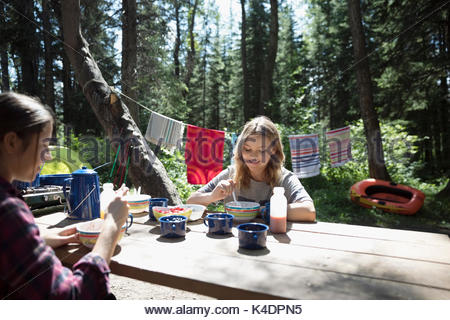 Teenage girl friends eating breakfast at sunny outdoor school campsite picnic table - Stock Photo
