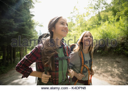 Curious, smiling teenage girl friends with backpacks hiking in woods - Stock Photo