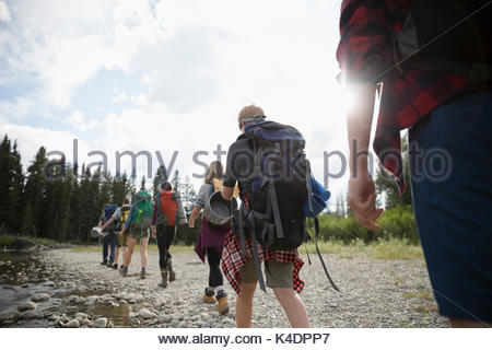 Teenage outdoor school students hiking along stream in woods - Stock Photo