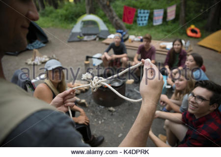Male teacher showing teaching teenage outdoor school students how to tie a knot in rope at campsite - Stock Photo