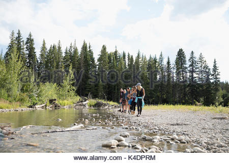 Female teacher and teenage outdoor school students exploring at stream in woods - Stock Photo