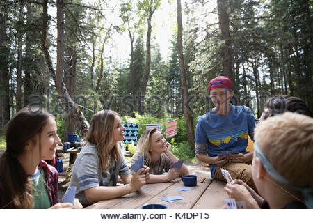 Teenage outdoor school students playing cards at campsite picnic table - Stock Photo