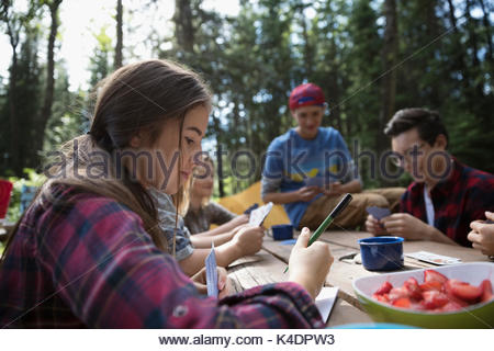Teenage outdoor school girl student writing at campsite picnic table - Stock Photo