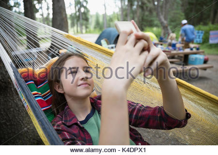 Teenage girl relaxing, texting with cell phone in hammock at outdoor school campsite - Stock Photo