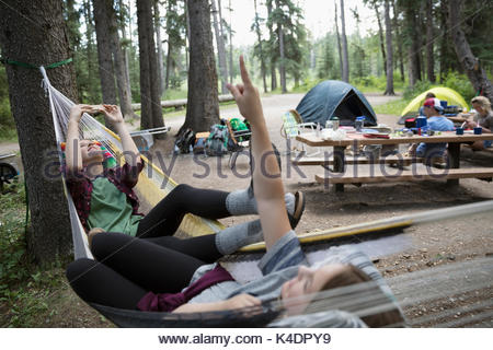 Teenage girl friends relaxing, laying in hammocks at outdoor school campsite - Stock Photo
