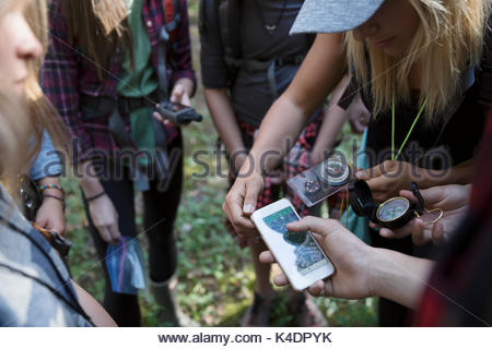 Female teacher and teenage outdoor school students using compass and smart phone gps, hiking - Stock Photo