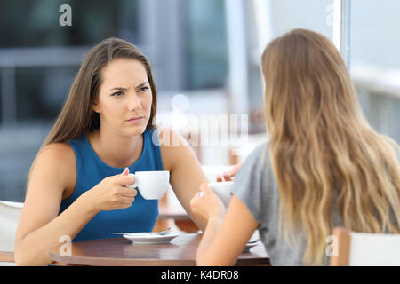 Two serious friends having a conversation sitting in a bar terrace - Stock Photo