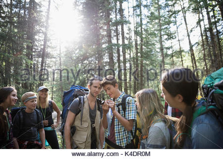 Male teacher and teenage outdoor school students exploring, hiking in woods below trees - Stock Photo