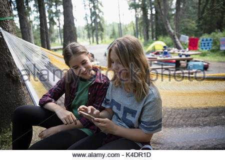 Teenage girl friends texting with cell phone in hammock at outdoor school campsite - Stock Photo