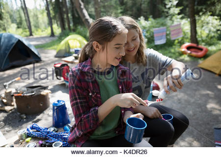 Teenage girl friends brushing teeth with toothbrushes and mugs at outdoor school campsite - Stock Photo
