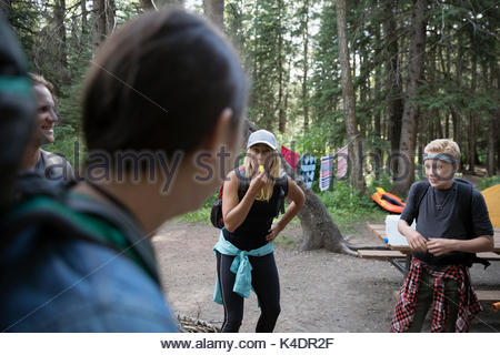 Female outdoor school teacher blowing whistle at students at campsite in woods - Stock Photo