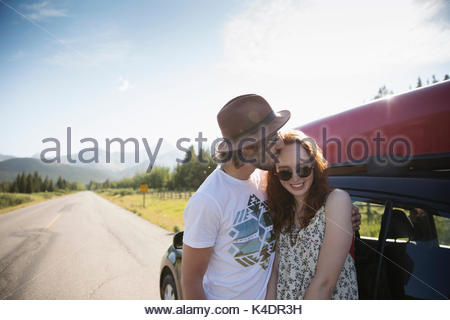 Affectionate young couple kissing outside car with canoe at sunny summer rural roadside - Stock Photo