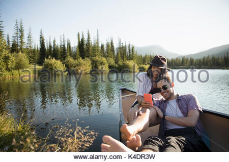Young couple with cell phone relaxing in canoe on sunny summer lake - Stock Photo