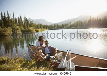 Young couple relaxing in canoe on sunny summer lake - Stock Photo