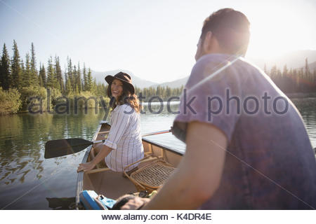 Young couple in canoe on sunny summer lake - Stock Photo