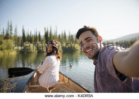 Portrait smiling young couple taking selfie in canoe on sunny summer lake - Stock Photo