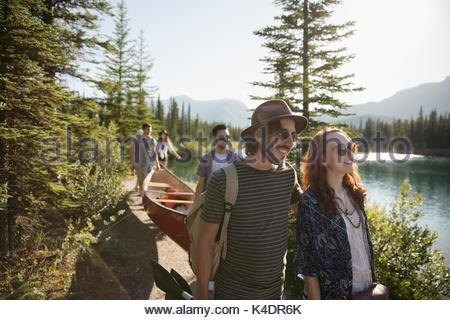 Friends carrying canoe along sunny summer lake - Stock Photo