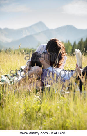 Affectionate young couple kissing and reading book in sunny summer rural field - Stock Photo
