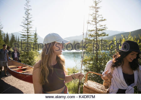 Female friends carrying fishing rods, picnic basket and canoe along sunny summer lake - Stock Photo