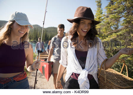 Smiling friends carrying fishing rod, picnic basket and canoes at sunny lakeside - Stock Photo