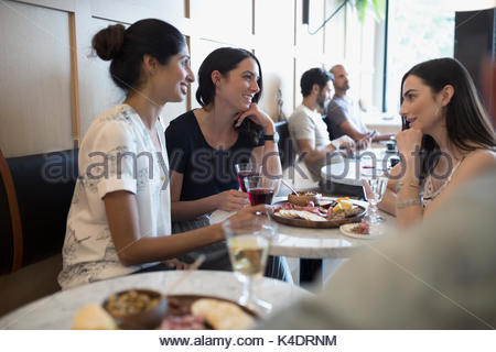 Women friends drinking wine at cafe table - Stock Photo